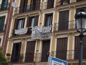 """La pancarta pequeña dice """"Defendamos nuestro barrio""""."""